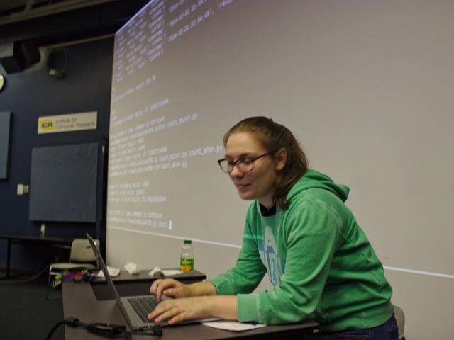 Elana Hashman, typing on a laptop at a podium in front of a screen displaying a command line prompt and Python code