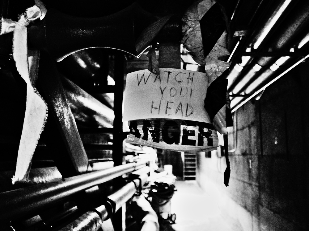 Black and white image down a steam tunnel. A sign says 'WATCH YOUR HEAD - DANGER'.